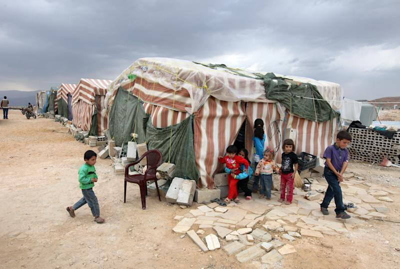 In this Tuesday, Oct. 2, 2012 photo, Syrian refugees children stand in front of their tents at a refugee camp in Arsal, a Sunni Muslim town eastern Lebanon near the Syrian border, has become a safe haven for war-weary Syrian rebels and hundreds of refugee families. Many in Arsal support the rebels, but the town's stand is risking heightened tensions with its Shiite Muslim neighbors in an area controlled by Hezbollah, a militia that backs the Syrian regime. Deepening sectarian rifts are one of the ways in which Syria's 18-month-old conflict is destabilizing an already volatile region. (AP Photo/Bilal Hussein)