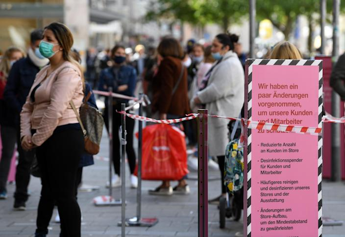 Customers wait in line in Munich after the coronavirus lockdown has been eased around the country and companies open some of their stores, May 12. (Andreas Gebert/Reuters)