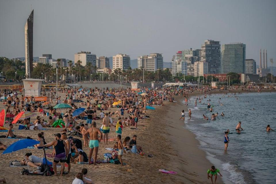 People enjoy the hot weather on a beach in Barcelona, Spain  (AP)