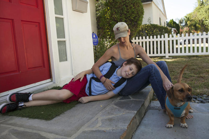 In this photo taken Monday, Aug. 13, 2012, Joyce Asner hugs her son Will, 9, who is autistic outside their home in the Tarzana district of Los Angeles. Public school districts are seeing higher proportions of children with special needs due to declining enrollment and charter schools that do not accept as many kids with disabilities, especially more severe disabilities. This raises a question of equitable access for these kids, as well as cost issues for school districts. (AP Photo/Damian Dovarganes)