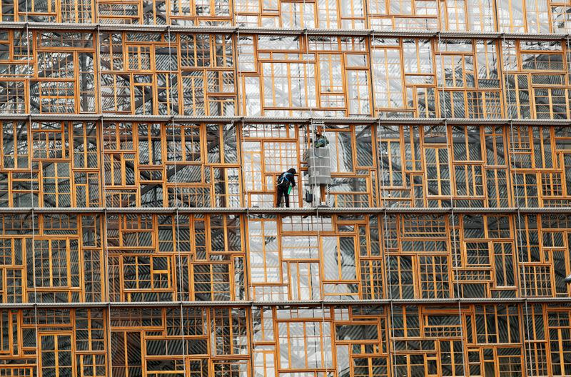 FILE PHOTO: Window cleaners work on the facade of the European Union Council building in Brussels