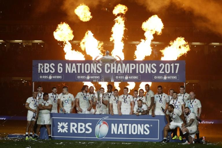 England players celebrate with the trophy after winning the Six Nations Championship on the pitch after the Six Nations international rugby union match between Ireland and England at the Aviva Stadium in Dublin on March 18, 2017