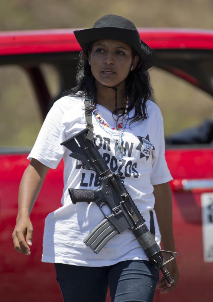 An armed female member of the Self-Defense Council of Michoacan (CAM) patrols a checkpoint set up by the self-defense group in Chuquiapan on the outskirts of the seaport of Lazaro Cardenas in western Mexico, Friday, May 9, 2014. Mexico's government plans to begin demobilizing the vigilante movement that largely expelled the Knights Templar cartel when state and local authorities couldn't. A ceremony on Saturday will mark the registering of thousands of guns by the federal government and an agreement that the self-defense groups will either join a new official rural police force or return to their normal lives and act as voluntary reserves when called on. (AP Photo/Eduardo Verdugo)