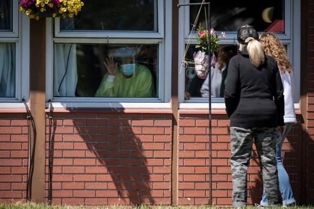 Friends and family members of residents at Extendicare Guildwood in Toronto visit their loved ones through windows, on June 12, 2020. (Evan Mitsui/CBC - image credit)