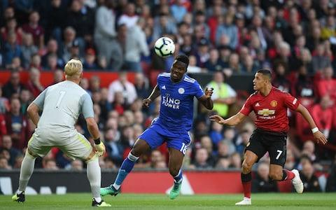 Manchester United's Chilean striker Alexis Sanchez (R) vies with Leicester City's Ghanaian midfielder Daniel Amartey (C) as Leicester City's Danish goalkeeper Kasper Schmeichel looks on during the English Premier League football match between Manchester United and Leicester City at Old Trafford - Credit: AFP