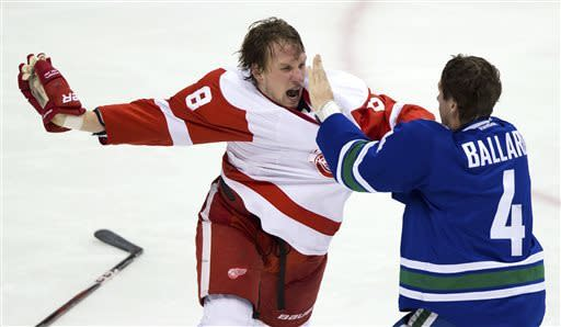 Detroit Red Wings' Justin Abdelkader, left, and Vancouver Canucks' Keith Ballard fight during the second period of an NHL hockey game in Vancouver, British Columbia, on Saturday, April 20, 2013. (AP Photo/The Canadian Press, Darryl Dyck)