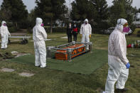 Cemetery workers wearing protective gear against the new coronavirus, walk after carrying the coffin of 72-year-old Monica Lagos to her grave at the Manantial cemetery in Santiago, Chile, Monday, June 15, 2020. According to her grandaughter Ninoska Vasquez, who works as an assistant at a health center, Lagos died from complications related to COVID-19. (AP Photo/Esteban Felix)