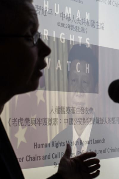 An image of President Xi Jinping is seen as Sophie Richardson, China director at Human Rights Watch speaks at the Foreign Correspondents' Club in Hong Kong on May 13, 2015, following the release of a report of police torture of criminal suspects (AFP Photo/Anthony Wallace)