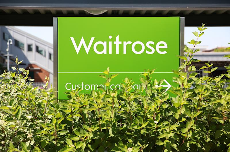 Haywards Heath, UK - August 7, 2020: A Waitrose store sign shot at eye-level in foliage