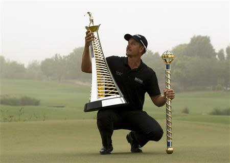 Henrik Stenson of Sweden poses with his trophies after winning the DP World Tour Championship in Dubai November 17, 2013. World number three Stenson blasted a final round 64 to clinch the DP World Tour Championship on Sunday, also topping Europe's money list for 2013 after his six-stroke victory in the desert finale. REUTERS/Caren Firouz