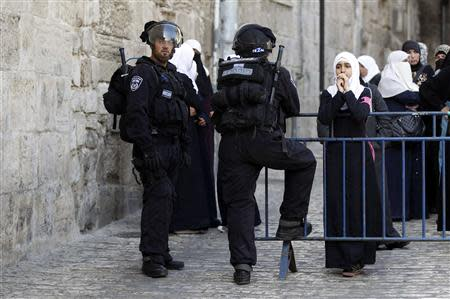 A Palestinian woman looks on as Israeli policemen prevent people from entering the compound which houses al-Aqsa mosque and is known to Muslims as Noble Sanctuary and to Jews as Temple Mount, in Jerusalem's Old City April 16, 2014. REUTERS/Ammar Awad