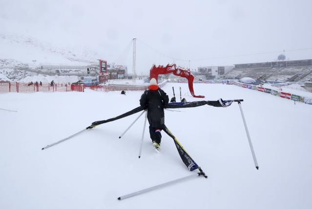 A course crew member carries away poles as an alpine ski, men's World Cup giant slalom is canceled due to bad weather, in Soelden, Austria, Sunday, Oct. 27, 2018. (AP Photo/Alessandro Trovati)