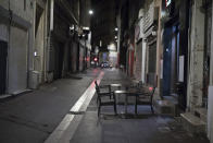 Tables sit empty in Marseille, southern France, Saturday, Oct. 17, 2020. France is deploying 12,000 police officers to enforce a new curfew that came into effect Friday night for the next month to slow the virus spread, and will spend another 1 billion euros to help businesses hit by the new restrictions. (AP Photo/Daniel Cole)