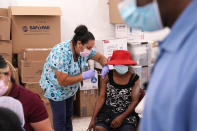 FILE - In this April 10, 2021, file photo, registered nurse Ashleigh Velasco, left, administers the Johnson & Johnson COVID-19 vaccine to Rosemene Lordeus, right, at a clinic held by Healthcare Network in Immokalee, Fla. With coronavirus shots now in the arms of nearly half of American adults, the parts of the U.S. that are excelling and those that are struggling with vaccinations are starting to look like the nation's political map: deeply divided between red and blue states. (AP Photo/Lynne Sladky, File)