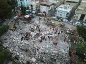 An aerial view shows rescue workers searching for survivors at a collapsed building after an earthquake in Izmir