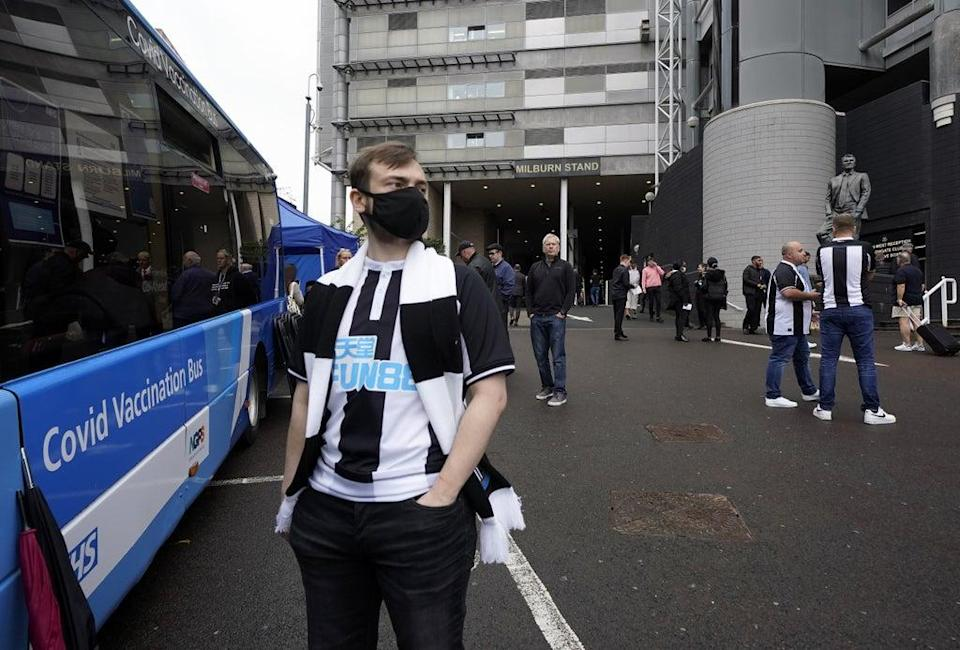A Newcastle United fan waits for a Covid-19 dose at a vaccination bus outside the St James' Park stadium (Owen Humphreys/PA) (PA Wire)