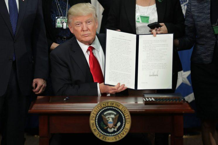 Trump displays one of the four executive orders he signed during a visit to the Department of Homeland Security on Wednesday. (Chip Somodevilla/Getty Images)