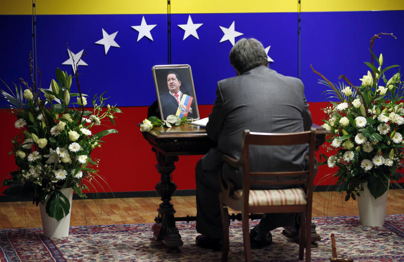 A man writes a note in a book of condolence at the embassy of Venezuela in Berlin, Germany, Wednesday, March 6, 2013, to honor deceased President of Venezuela, Hugo Chavez. (AP Photo/Michael Sohn)