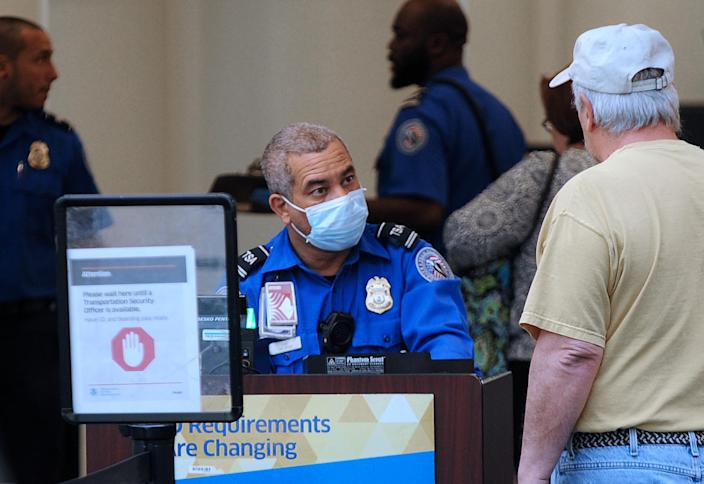 A TSA officer wears a protective mask while screening travelers at Orlando International Airport. (Paul Hennessy/Echoes Wire/Barcroft Media via Getty Images)