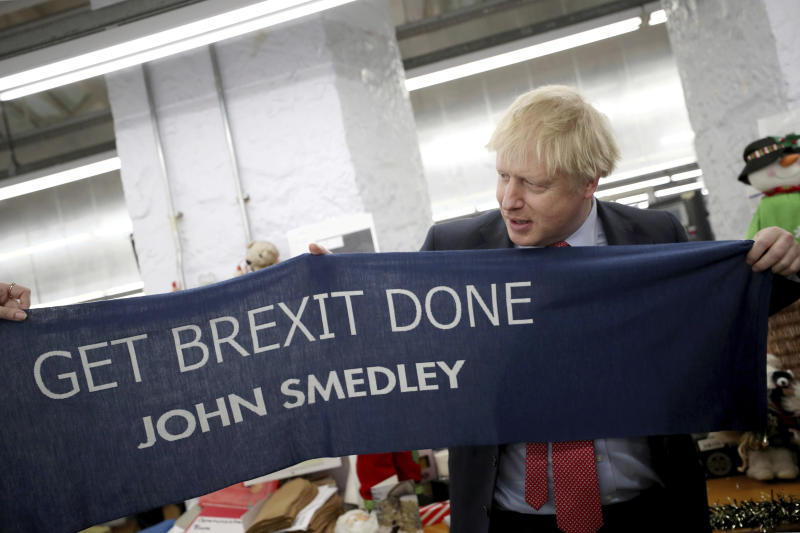 "Britain's Prime Minister Boris Johnson hold a scarf with slogan ""Get Brexit Done"" as he visits John Smedley Mill in Matlock, England, Thursday, Dec. 5, 2019. Britain is holding a general election a week from now and fractures are emerging within jittery political parties unsure how a volatile electorate will judge them. Conservative Prime Minister Boris Johnson and main opposition Labour Party leader Jeremy Corbyn both faced criticism of their moral character. (Hannah McKay/Pool Photo via AP)"
