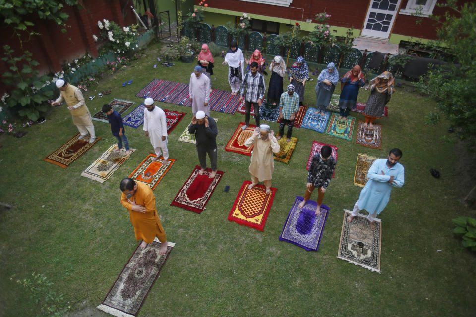 Kashmiri Muslims offer Eid prayers in the premises of a residential building in Srinagar, Indian controlled Kashmir, Sunday, May 24, 2020. The holiday of Eid al-Fitr, the end of the fasting month of Ramadan, a usually joyous three-day celebration has been significantly toned down as coronavirus cases soar. (AP Photo/Mukhtar Khan)