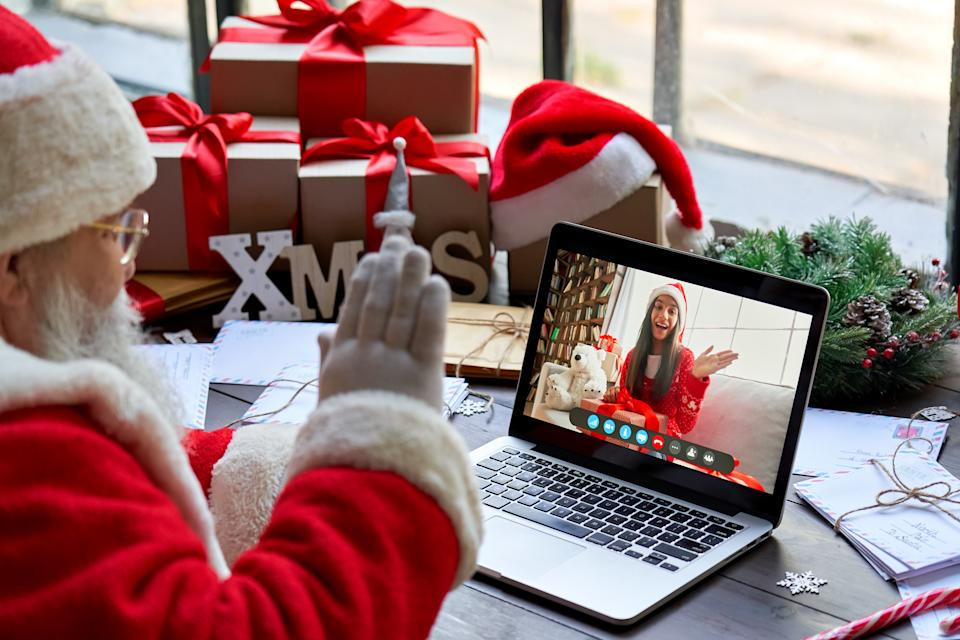 Over shoulder view of Santa Claus video calling kid girl on laptop greeting child by webcam talk open Christmas gift box in virtual online chat meeting using computer sit at workshop table on xmas.