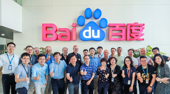 Baidu researchers with their thumbs up in front of Baidu logo.