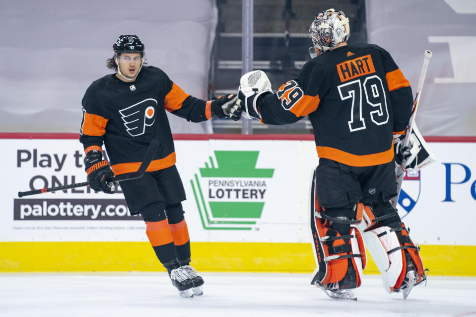 Philadelphia Flyers' Travis Konecny, left, celebrates his goal with goaltender Carter Hart, right, during the first period of an NHL hockey game against the Pittsburgh Penguins, Friday, Jan. 15, 2021, in Philadelphia. (AP Photo/Chris Szagola)