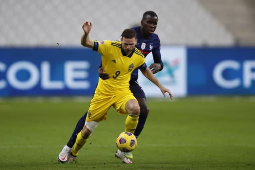 Sweden's Marcus Berg, foreground, controls the ball as France's N'Golo Kante holds him during the UEFA Nations League soccer match between France and Sweden at the Stade de France stadium in Saint-Denis, northern Paris, Tuesday, Nov. 17, 2020. (AP Photo/Francois Mori)