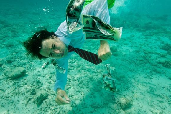Businessman collecting money swimming underwater, wearing formal clothes.