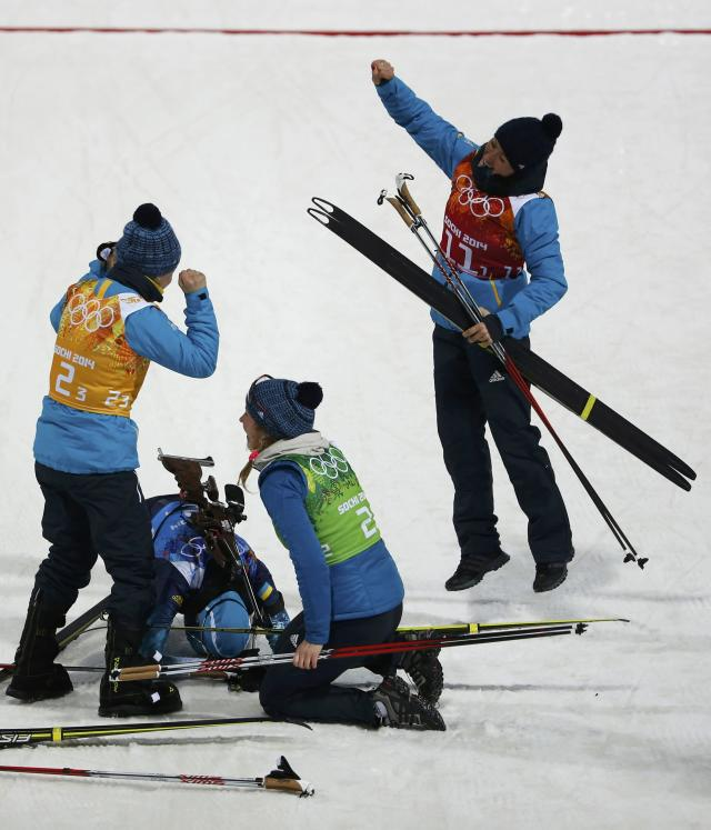 Ukraine's Valj Semerenko, Olena Pidhrushna, Juliya Dzhyma and Vita Semerenko (L-R) celebrate after crossing the finish line to win the women's biathlon 4x6 km relay event at the Sochi 2014 Winter Olympic Games February 21, 2014. REUTERS/Stefan Wermuth (RUSSIA - Tags: OLYMPICS SPORT BIATHLON)