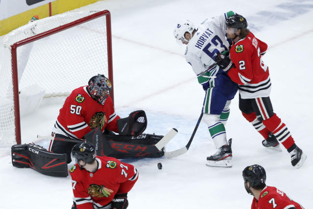 Chicago Blackhawks goaltender Corey Crawford (50) makes a save as defenseman Duncan Keith (2) keeps Vancouver Canucks center Bo Horvat from getting a rebound shot during the second period of an NHL hockey game Thursday, Nov. 7, 2019, in Chicago. (AP Photo/Charles Rex Arbogast)