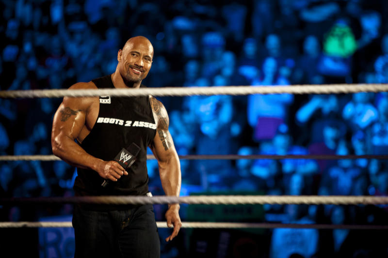 Dwayne Johnson, aka The Rock, holds a microphone in a WWE ring.
