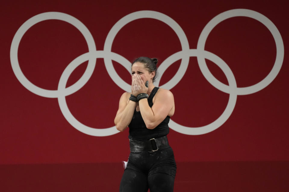 Maude G. Charron of Canada cries after the last lift in the women's 64kg weightlifting event, at the 2020 Summer Olympics, Tuesday, July 27, 2021, in Tokyo, Japan. (AP Photo/Luca Bruno)