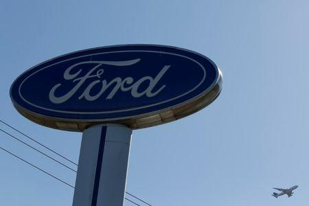 FILE PHOTO: An airplane flies above a Ford logo in Colma, California