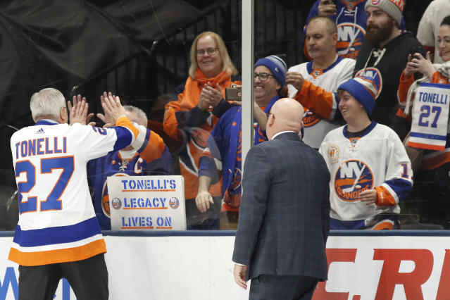 Former New York Islander John Tonelli, left, greets a fan on the other side of the glass as he leaves the ice following his jersey retirement ceremony Friday, Feb. 21, 2020, in Uniondale, N.Y. (AP Photo/Kathy Willens)