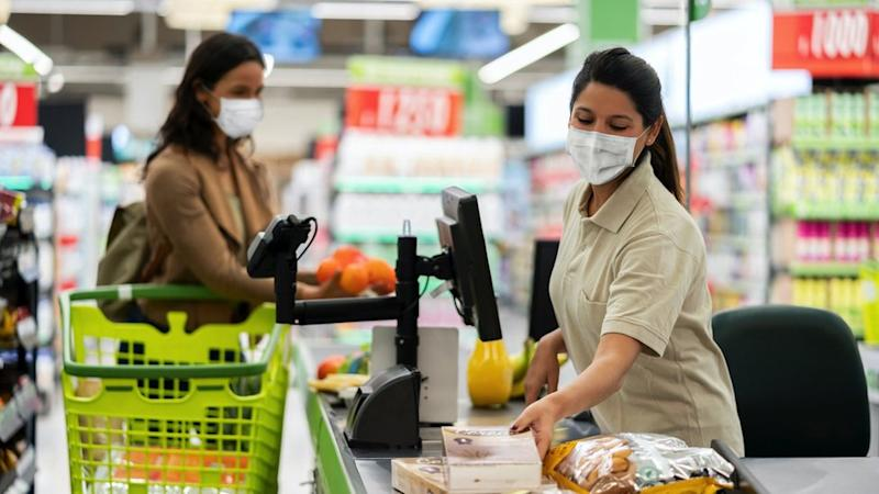 A woman shopping for food wears a face mask, as does the cashier