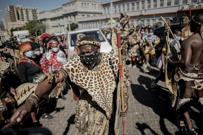 A Zulu mourner, clad in traditional leopardskin, cleared the way for the hearse in front of the morgue