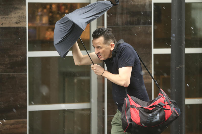 A man struggles with the wind and rain in Sydney.