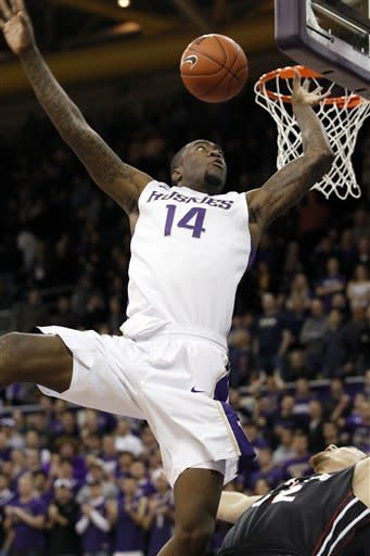 Washington's Tony Wroten (14) goes flying after fouling Cal State Northridge's Michael Lizarraga in the first half of an NCAA college basketball game Thursday, Dec. 22, 2011, in Seattle. (AP Photo/Elaine Thompson)