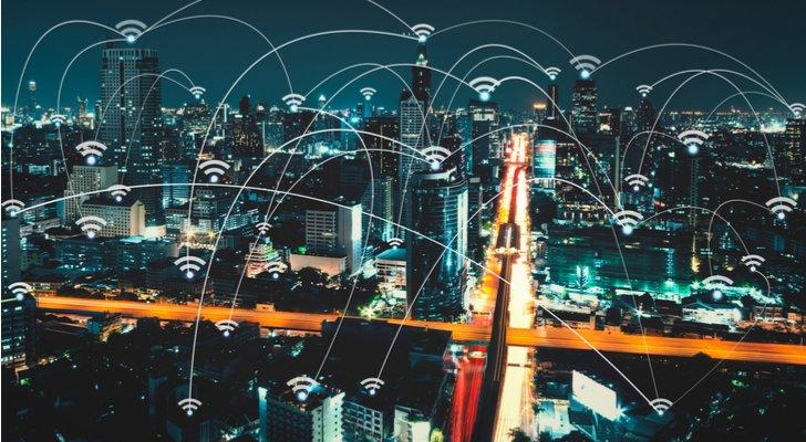 Image of a nighttime cityscape that's connected by various wifi-marked signals