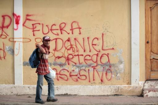 "A Nicaraguan man walks by a sign reading ""Out murderer Daniel Ortega"" in Masaya city on May 12, 2018, during nation-wide protests demanding the ouster of Ortega, a former revolutionary leader, as president"