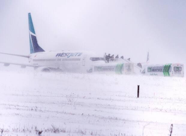 Passengers disembark a WestJet aircraft that skidded off the runway at Halifax Stanfield International Airport on Sunday, Jan. 5, 2020. No passengers or crew were injured. (Andrew Vaughan/The Canadian Press - image credit)