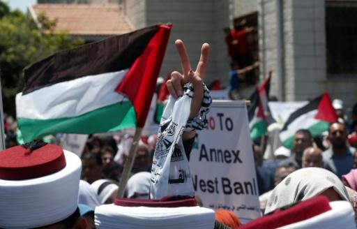 "A Palestinian demonstrator in Gaza City flashes the victory sign in a ""Day of Rage"" to protest Israel's plan to annex parts of the occupied West Bank"