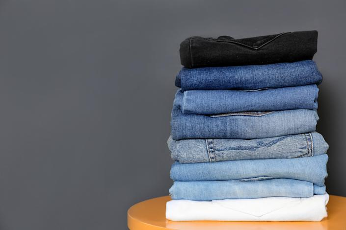 Stack of different jeans on table against gray background. Space for text