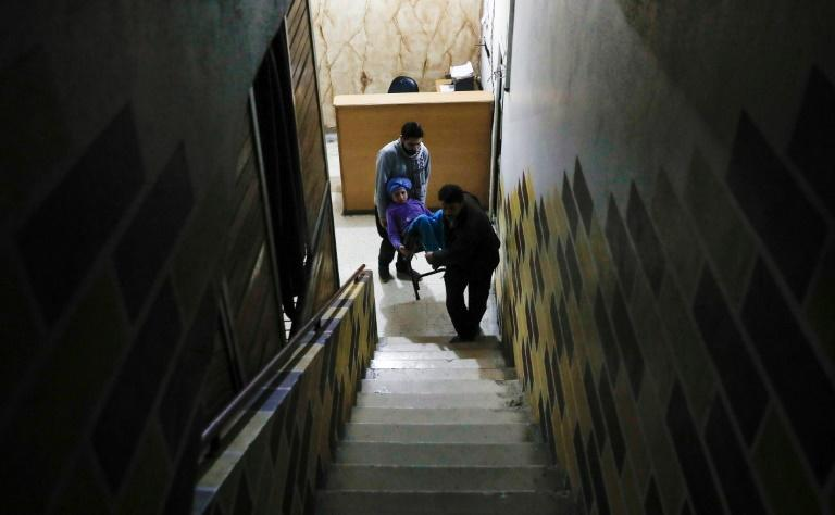 Two men carry 14-year-old Dania, who suffers from renal insufficiency, to have her dialysis inside a basement-turned-clinic in the rebel-held Syrian town of Douma, on the outskirts of the capital Damascus, on March 16, 2017