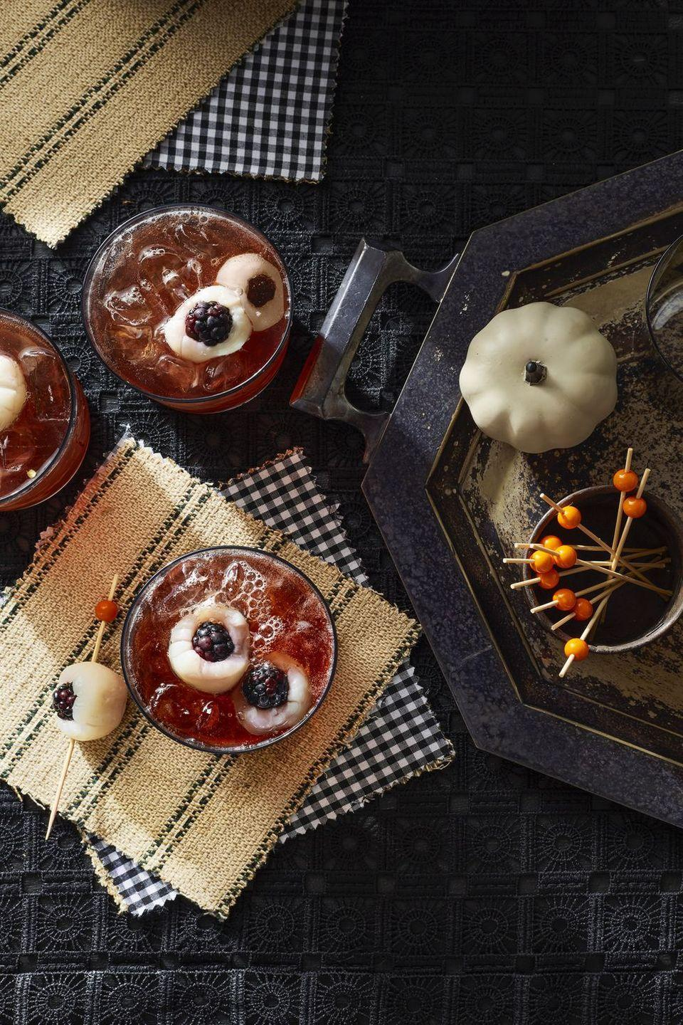 "<p>I spy an eyeball in my drink! Have no fear, they're actually lychees stuffed with blueberries.</p><p><em><a href=""https://www.countryliving.com/food-drinks/g2640/halloween-cocktails/?slide=2"" rel=""nofollow noopener"" target=""_blank"" data-ylk=""slk:Get the recipe from Country Living »"" class=""link rapid-noclick-resp""> Get the recipe from Country Living »</a></em></p>"