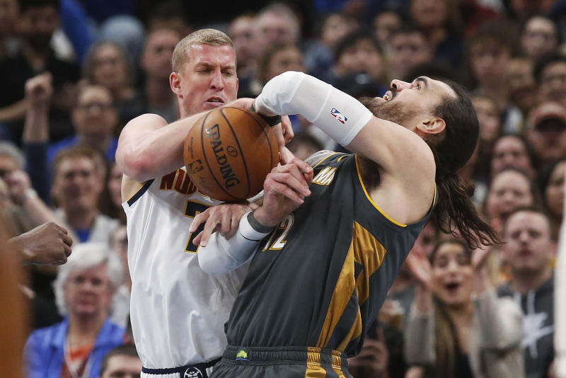 Denver Nuggets forward Mason Plumlee, left, knocks the ball away from Oklahoma City Thunder center Steven Adams, right, in the first half of an NBA basketball game Friday, Feb. 21, 2020, in Oklahoma City. (AP Photo/Sue Ogrocki)