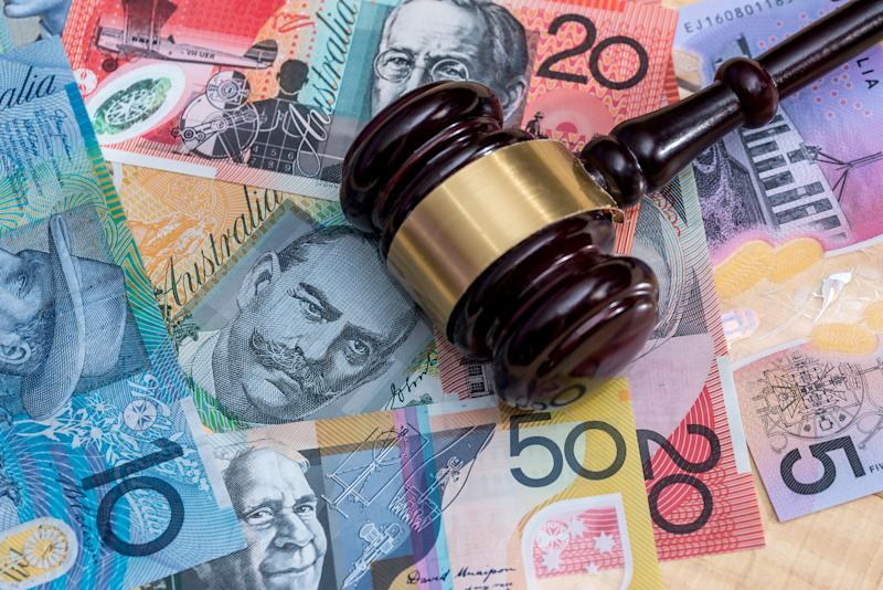 Pictured: Property auctioneer's gavel on pile of Australian cash. Image: Getty