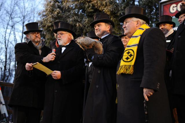 PUNXSUTAWNEY, PA - FEBRUARY 2: Groundhog handler John Griffiths (2nd-R) holds Punxsutawney Phil while members of the Inner Circle read the proclamation after Phil did not see his shadow predicting an early spring during the 125th annual Groundhog Day festivities on February 2, 2011 in Punxsutawney, Pennsylvania. Groundhog Day is a popular tradition in the United States and Canada. A smaller than usual crowd this year of less than 15,000 people spent a night of revelry awaiting the sunrise and the groundhog's exit from his winter den. If Punxsutawney Phil sees his shadow he regards it as an omen of six more weeks of bad weather and returns to his den. Early spring arrives if he does not see his shadow causing Phil to remain above ground. (Photo by Jeff Swensen/Getty Images)